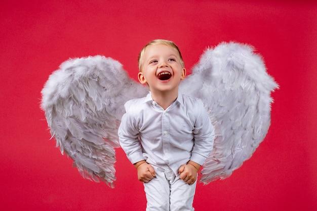 Мальчик-ангел с белыми крыльями смеется, возбужденные дети-ангелы смеются, милый возбужденный ребенок с ...