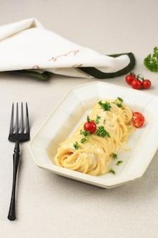 까르보나라 크림 소스를 곁들인 엔젤 헤어 파스타, 파마산 치즈를 곁들인 알라 까르보나라 스파게티. 직사각형 접시에 제공