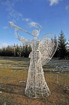 Ангел играет на трубе из лампочек, прикрепленных к металлическому корпусу