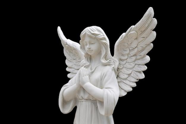 검은 배경에 고립 된 천사 조각상입니다.