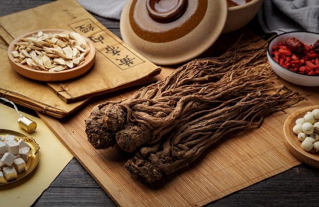 アンジェリカ、テーブルの上の古代漢方薬の本とハーブ。