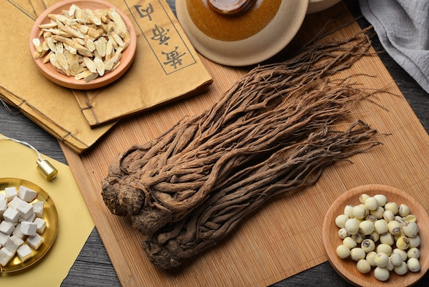 Angelica,ancient chinese medicine books and herbs on the table.