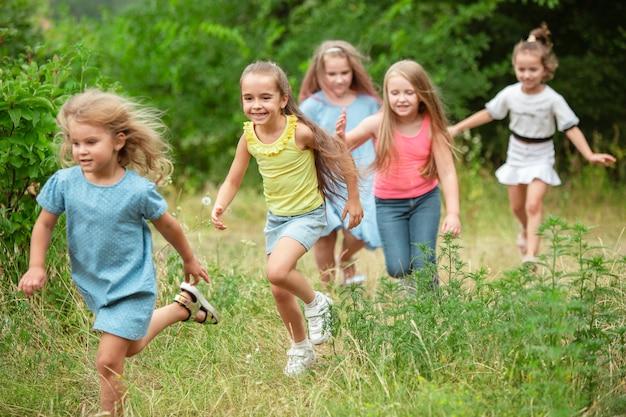 Ангелы. дети, дети бегают по зеленому лесу. веселые и веселые мальчики и девчонки играют, смеются, бегут по зеленому цветущему лугу. детство и лето, концепция искренних эмоций.