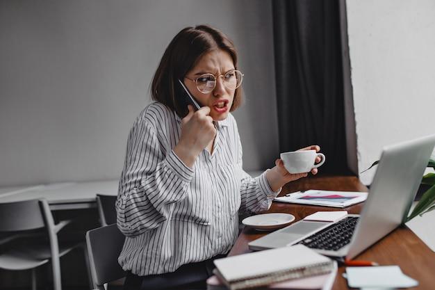 Imprenditore arrabbiato parlando al telefono con i subordinati. operaio femminile insoddisfatto in camicetta bianca che tiene tazza bianca al tavolo con il computer portatile.