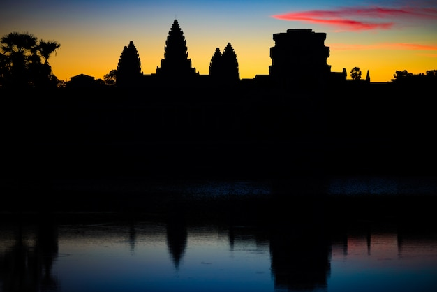 Angkor wat dramatic sky at dawn main facade silhouette reflection on water pond
