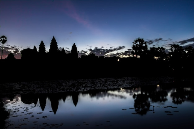 Angkor wat temple at sunrise reflecting in water