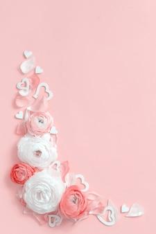 Угловая рамка из цветов, лепестков и сердечек ранункулюсов на светло-розовом виде сверху