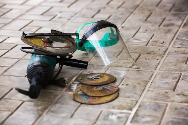アングルグラインダーとディスク、フェイスシールドマスク。作業環境、実際の条件。高品質の写真