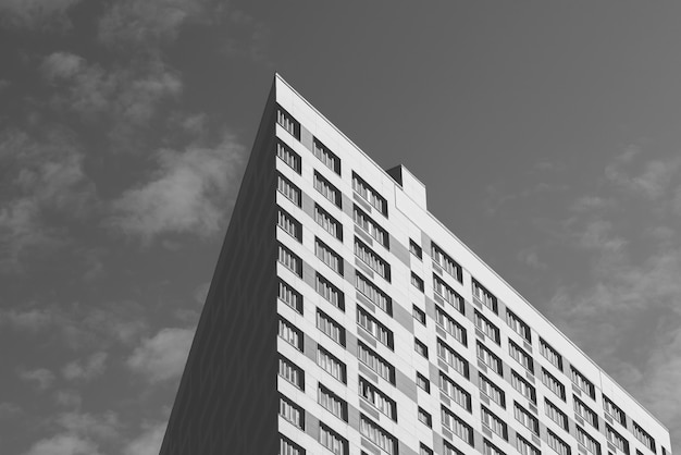 Angle of the skyscraper on the cloudy sky background. black and white.