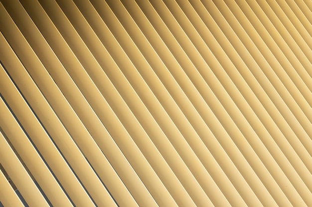 Angle view of beige or golden 3d stripes. louvre shutters like pattern.