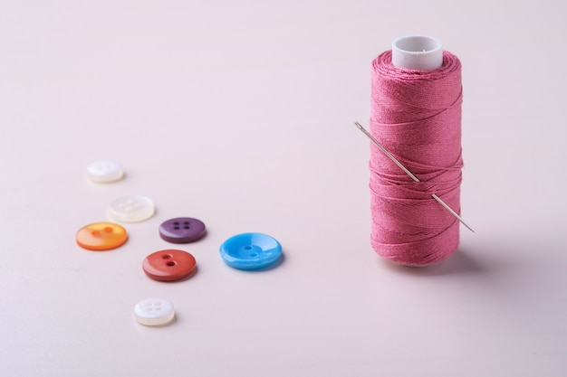 Angle view close up of pink thread coil with buttons and needle