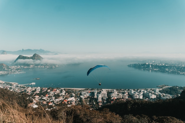 Угловой вид на море в окружении зданий и холмов с парапланами над ними в бразилии