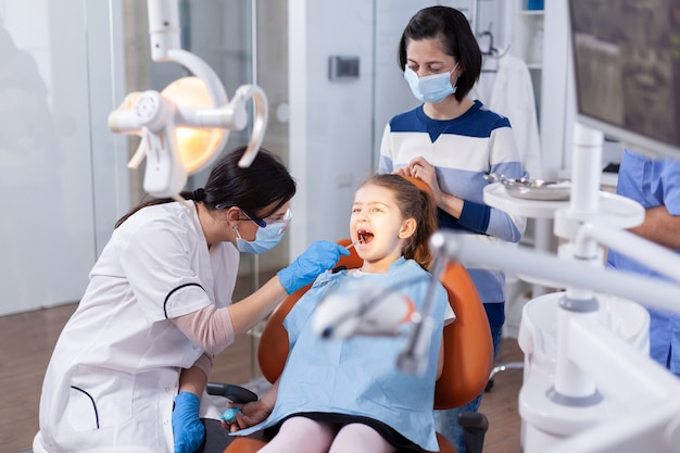Angled mirror used by dentist doctor on little girl with mouth open in dental office. dentistry specialist during child cavity consultation in stomatology office using modern technology.