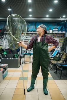 Рыболов в резиновом комбинезоне держит сеть, рыболовный магазин