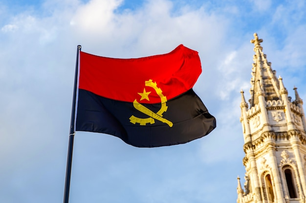 Angola flag waving in front of a blue sky.