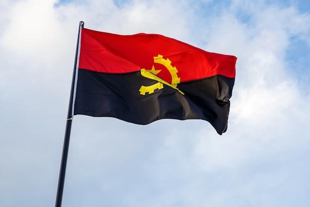 青い空の前で手を振っているアンゴラの旗。