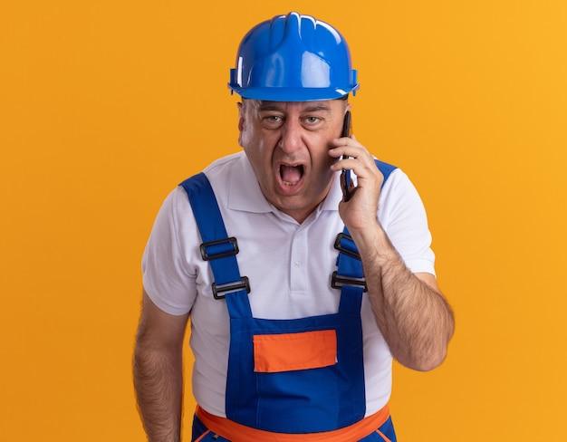 オレンジ色の壁に隔離された電話で誰かに叫ぶ制服を着た怒っている大人のビルダーの男