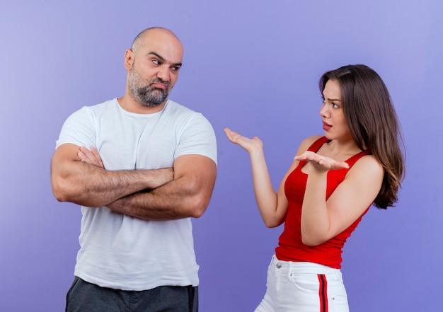Coppia adulta arrabbiata litigando tra di loro uomo accigliato in piedi con postura chiusa e donna dispiaciuta che mostra le mani vuote