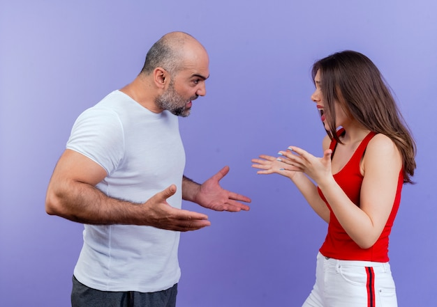 Angry adult couple standing in profile view both spreading hands and arguing with each other