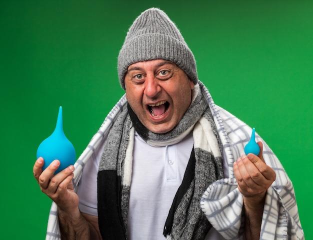 Arrabbiato adulto malato uomo caucasico con sciarpa intorno al collo indossando cappello invernale avvolto in plaid tenendo clisteri isolato sulla parete verde con spazio di copia