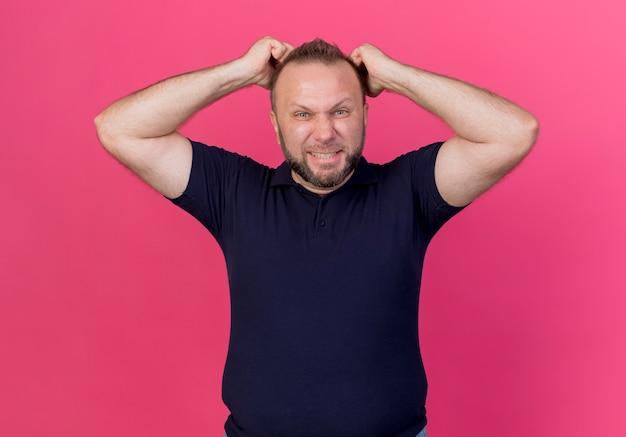 Uomo slavo adulto arrabbiato che mette i pugni sulla testa che sembra isolato sulla parete rosa