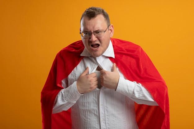 오렌지 벽에 고립 된 측면을보고 그것을 벗으려고 그의 셔츠를 잡는 안경을 쓰고 빨간 망토에 화가 성인 슬라브 슈퍼 히어로 남자