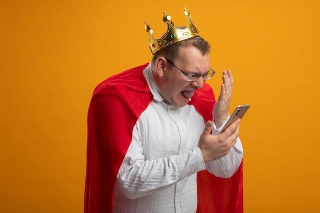 Arrabbiato adulto supereroe slavo uomo in mantello rosso con gli occhiali e corona che tiene e guardando il telefono cellulare tenendo la mano in aria isolata sulla parete arancione con lo spazio della copia