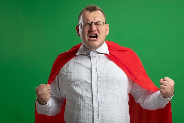 Сердитый взрослый супергерой в красной накидке в очках, сжимая кулаки с закрытыми глазами, изолирован на зеленой стене