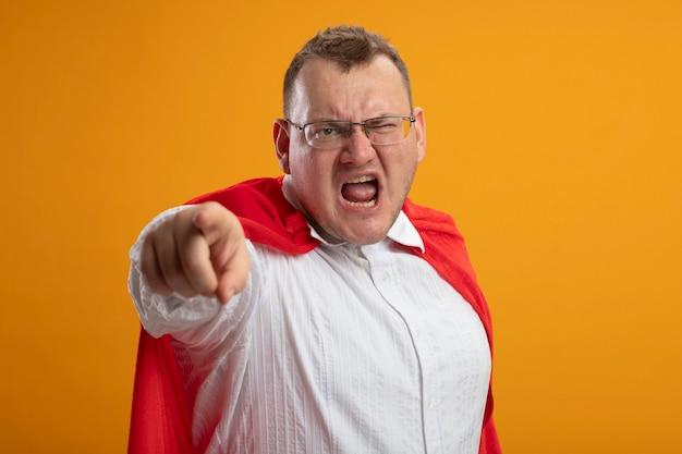 オレンジ色の壁に隔離された正面を見て、指している眼鏡をかけている赤いマントの怒っている大人のスーパーヒーローの男