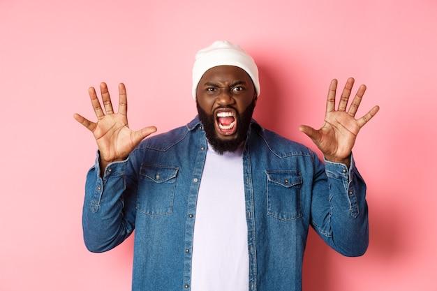 Ragazzo afroamericano arrabbiato in berretto, ti spaventa, ruggisce e urla, mostra le mani, in piedi su sfondo rosa