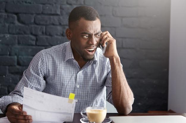 一枚の紙を保持している猛烈な表情を持つ正式なシャツで怒っているアフリカの実業家