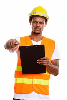 Angry african man construction worker holding clipboard while pointing finger