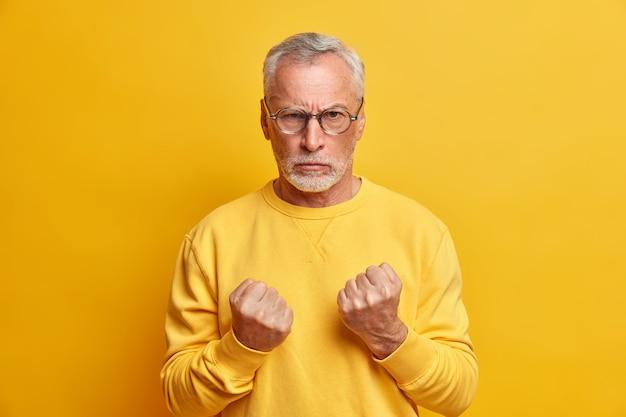 怒り狂った老人が拳を握りしめ、身を守るために怒りを表現し、黄色い壁にさりげなくポーズをとった正面を憤慨した表情で攻撃的に見える
