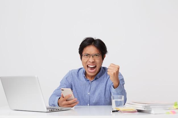 ノートパソコンや携帯電話で叫び、白い壁に拳のジェスチャーを示す眼鏡で怒っている攻撃的なアジアの若いビジネスマン