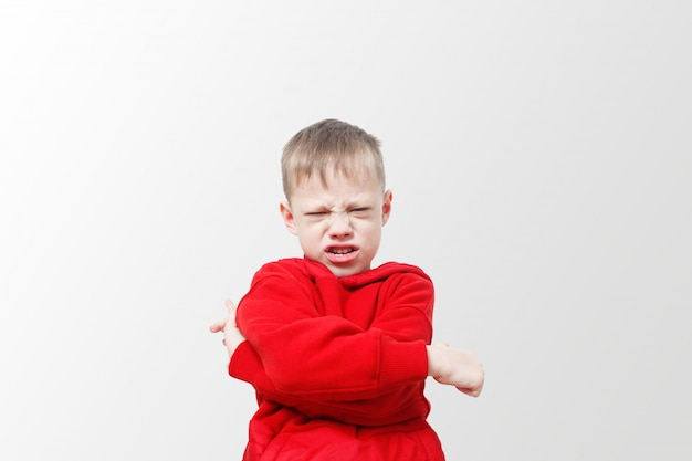 怒り狂った攻撃的な少年。赤いパーカーの子供は怒りを表現しています。興奮と眉をひそめる。ストレス、自閉症。動揺の欲求不満といたずら