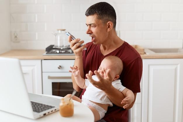 Arrabbiato aggressivo maschio bruna che indossa una maglietta marrone rossiccio in stile casual, inviando messaggi vocali, urlando al telefono, seduto al tavolo in cucina con sua figlia neonata.