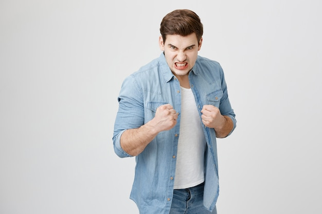 怒っている積極的な男が拳を握り締めて戦いの準備をする