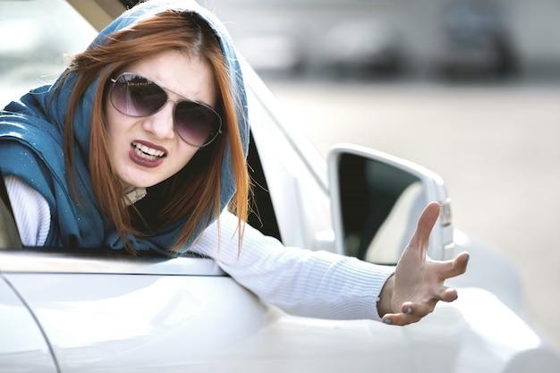Angry aggressive woman driving a car shouting at someone