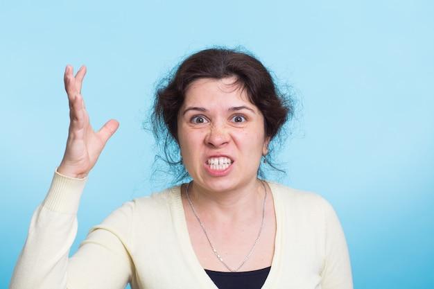 青い壁に怒っている攻撃的な女性