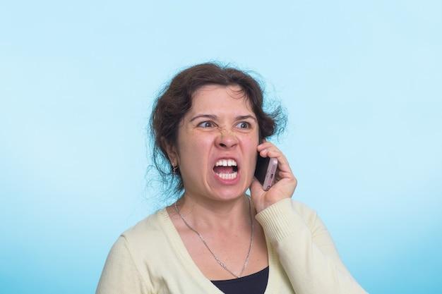 猛烈な表情で怒っている攻撃的な女性。