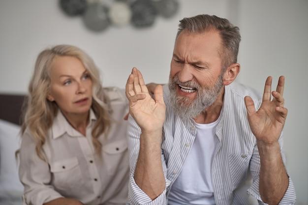 Злой взволнованный бородатый седой зрелый мужчина спорит со своей молчаливой супругой, сидящей позади него