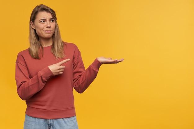 포즈 화가 깜짝 놀라게 젊은 여자가 copyspace에 손가락으로 나타냅니다, 빨간 스웨터를 입고