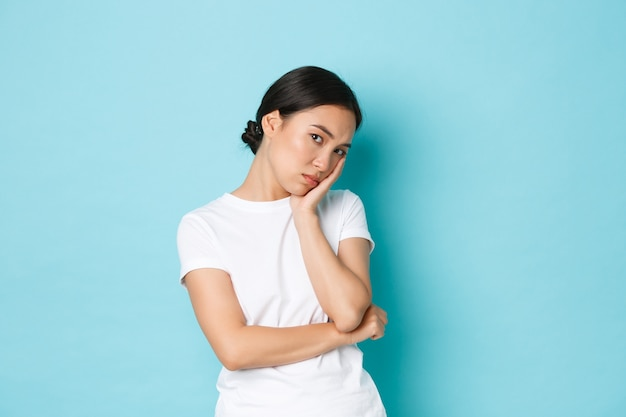 Злая и скучающая надутая милая азиатская девушка, опирающаяся на ладонь и равнодушно смотрящая, ведет себя не обеспокоенно, но хмурится, злится или обижается, стоит на синем фоне недовольно.