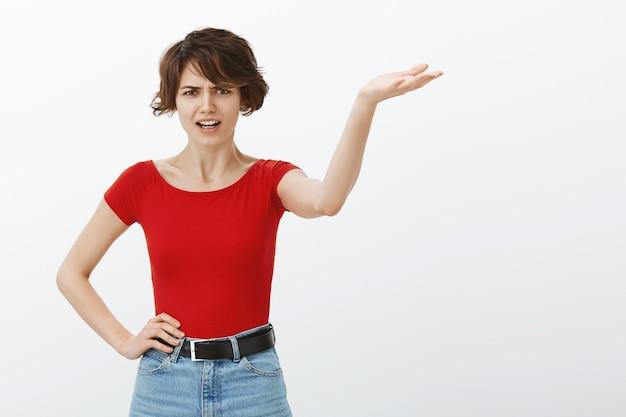 Злая и жалующаяся женщина спорит, указывая рукой вправо с безумным лицом