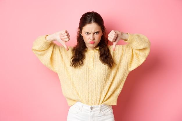 Сердитая и недовольная молодая девушка хмурится, показывает большие пальцы на что-то плохое, выражает неприязнь, оставляет отрицательный отзыв, расстроено стоит у розовой стены