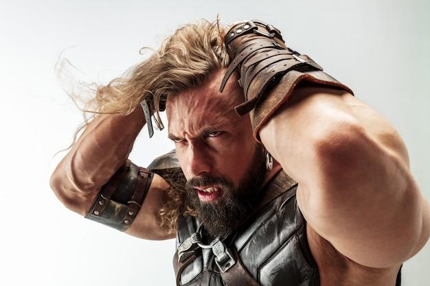 Злой и эмоциональный. светлые длинные волосы и мускулистая мужская модель в кожаном костюме викинга с косплеем большого молотка на белом фоне студии. фэнтезийный воин, античная концепция битвы.