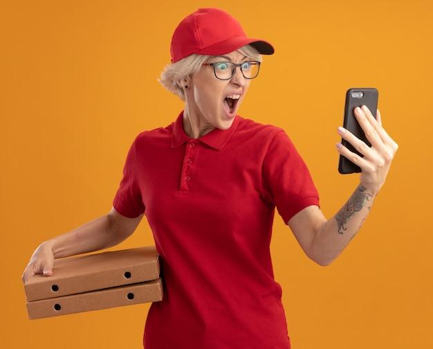 Сердитая и разочарованная молодая женщина-доставщик в красной форме и кепке в очках держит коробки для пиццы, глядя на свой смартфон, крича с агрессивным выражением лица, стоя над оранжевой стеной