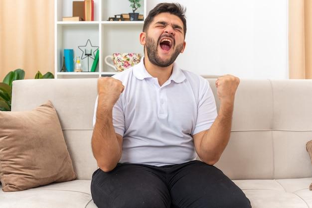 カジュアルな服を着た怒って欲求不満の若い男が拳を握りしめ、明るいリビング ルームのソファに座って大声で叫ぶ