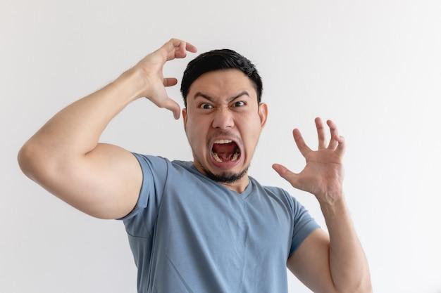 Сердитое и безумное лицо азиатского мужчины в голубой футболке на изолированном фоне.