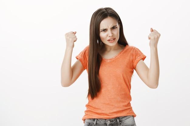 Злая и рассерженная девушка поднимает руки вверх, выглядит расстроенной, хочет драться, избивает кого-то